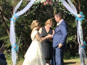 Bride and groom under arbor in outside wedding
