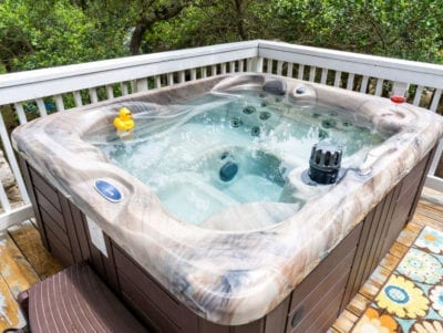 Outdoor hot tub on balcony in the trees