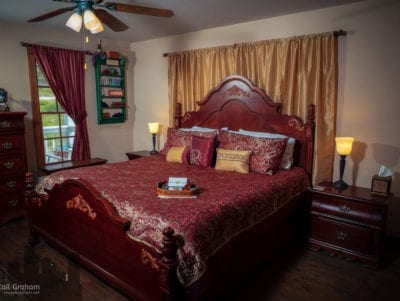King sized bed with red and gold bedspread