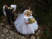 Bride twirling in her wedding dress as groom looks on